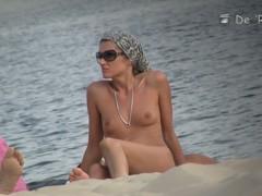 Cutie flaunts her perky tits in front of a nudist beach voyeur