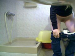 Blonde girl in jeans is peeing on the hidden cam in toilet