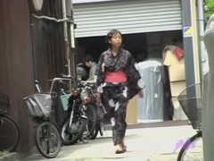 Cute Asian in a jukata has boob sharking on the street.