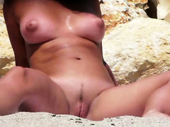 Bare breasty playgirl widens legs at the beach