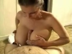 using her tits to please him