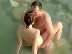 Outdoor voyeur pussy fucking in sea water with nude couple on public beach