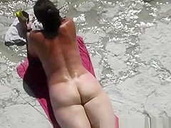 Nudist woman in her red towel sunbathing