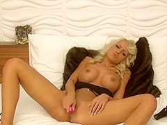 Voluptuous blonde bombshell lies on the bed and gives it to