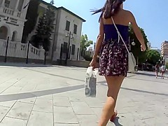 Cute girl protects her skirt from wind