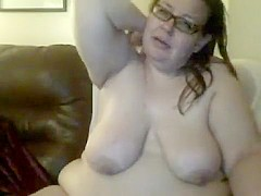Obese brunette in eyeglasses shows off her saggy boobs and