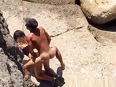 Couple spied in rocky beach having sex