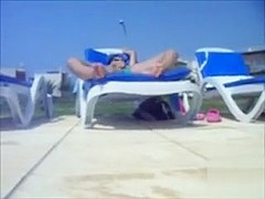 My wife in lounge chair stimulates her clitoris poolside