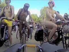 Group of nudists cycle through a town in their birthday suits