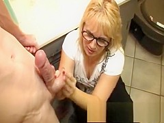 Lustful blonde mommy with glasses offers a young stud a nice handjob