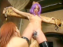 Lesbian mistress puts her slave on a cross to dominate her ass