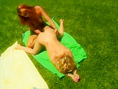 Blonde and redhead lesbians having fun with their new sex toy outside