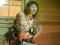Tied up Asian babe rides a fat dildo
