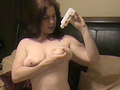 Milf pours lotion on her Big tits