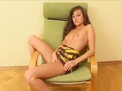 Shy brunette poses nude on armachair
