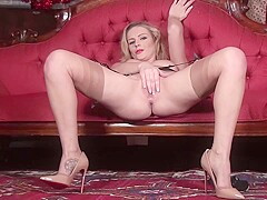 Sexy blonde milf in stockings, garter belt and high heels is rubbing her perfectly shaved pussy