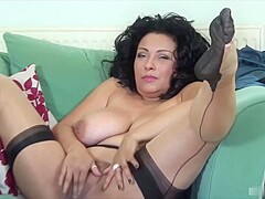 Hot mature brunette in erotic, black stockings is gently rubbing her shaved pussy and moaning